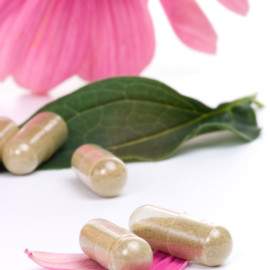 Closeup of Echinacea extract pills and fresh Echinacea flowers best suited for alternative medicine ads. Shallow DOF.
