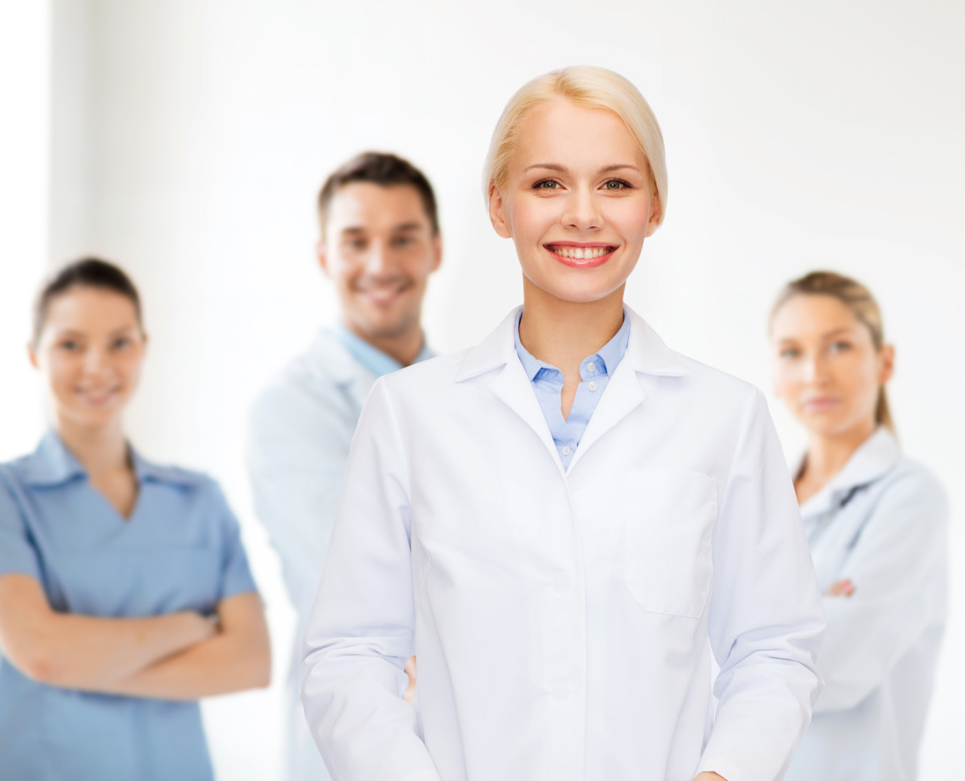 healthcare and medicine concept - smiling female doctor over group of medics in hospital