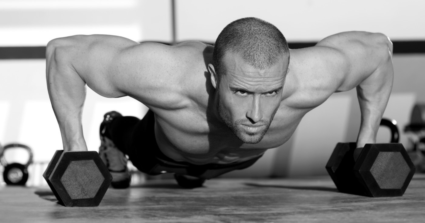 Gym man push-up strength pushup exercise with dumbbell in a crossfit workout
