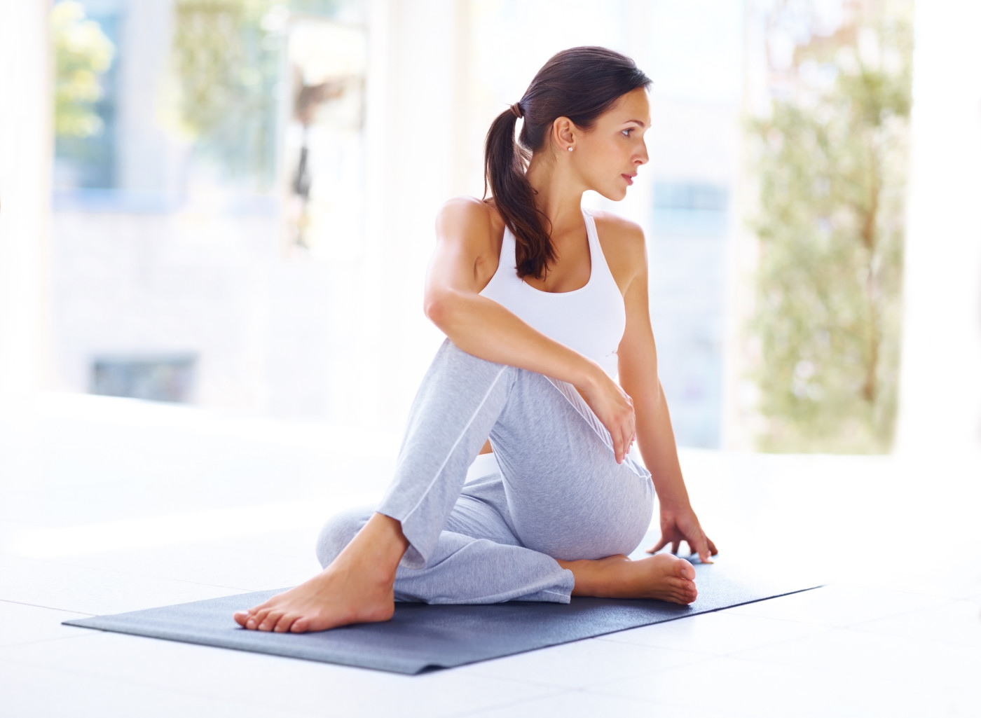 Portrait of healthy young woman doing yoga - Spine twisting pose