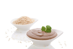 Tahini pasta and sesame seeds in white bowl isolated on white background. Hummus ingredients, mediterranean eating.