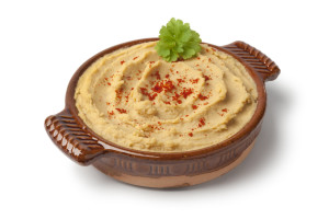 Bowl with hummus and chili pepper on white background