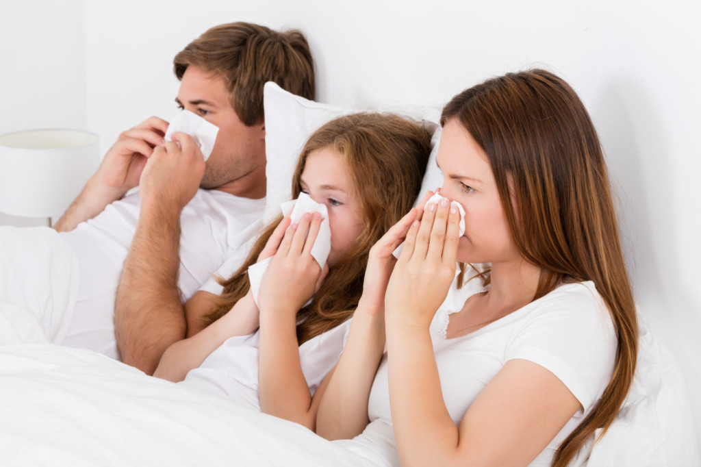 Family Lying On Bed Blowing Their Nose