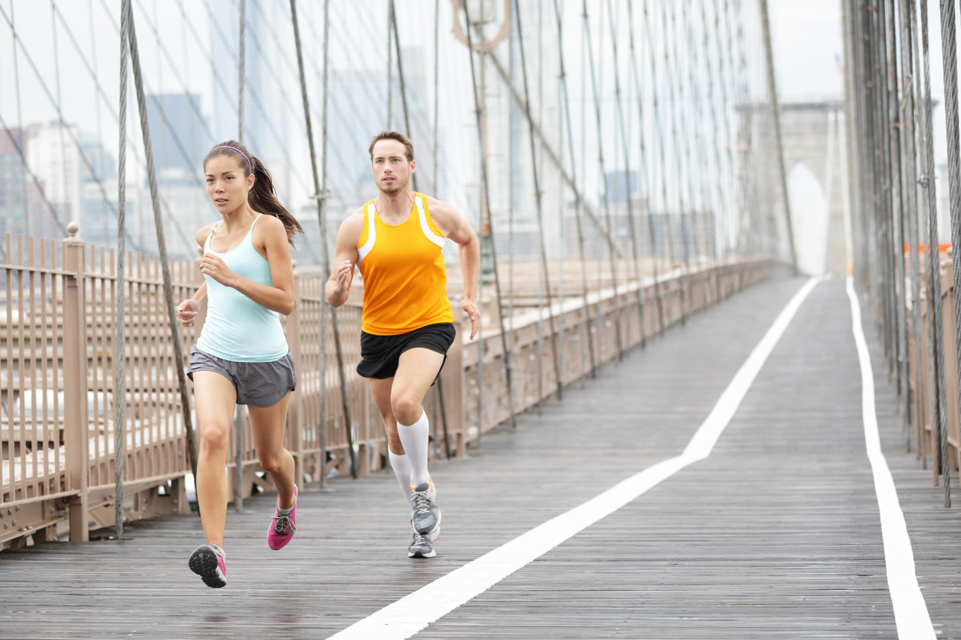 Running couple. Runners training outside. Asian woman and Caucasian man runner and fitness sport models jogging in full body showing Brooklyn Bridge, New York City, USA.