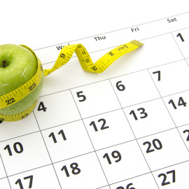 Dieting concept apple and tape measure on a calendar